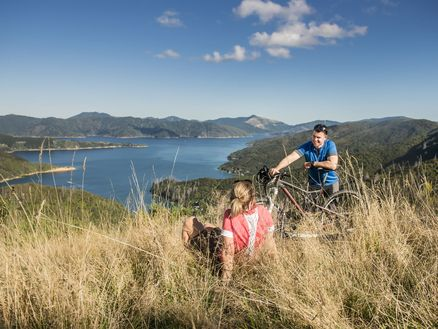 Mountain bikers rest overlooking Bay of Many Coves along Marlborough's Queen Charlotte Track in New Zealand. Copyright Destination Marlborough